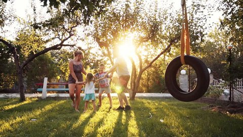 Children having fun holding hands with parents at park with tire swing in foreground and sunlight coming through trees. Having joined hands are turned around