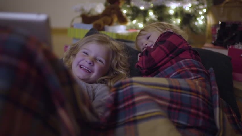 Brother And Sister Snuggle Up Under Christmas Tree And Watch A Funny Video On Tablet