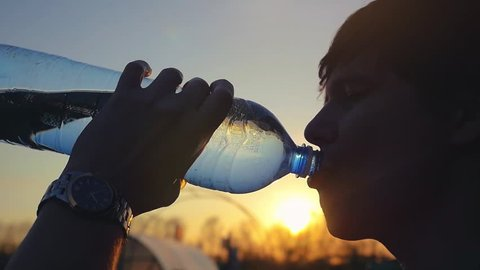 Young man drinking water from a plastic bottle in nature at wheat field. Man having water break at sunset in slowmotion. 1920x1080