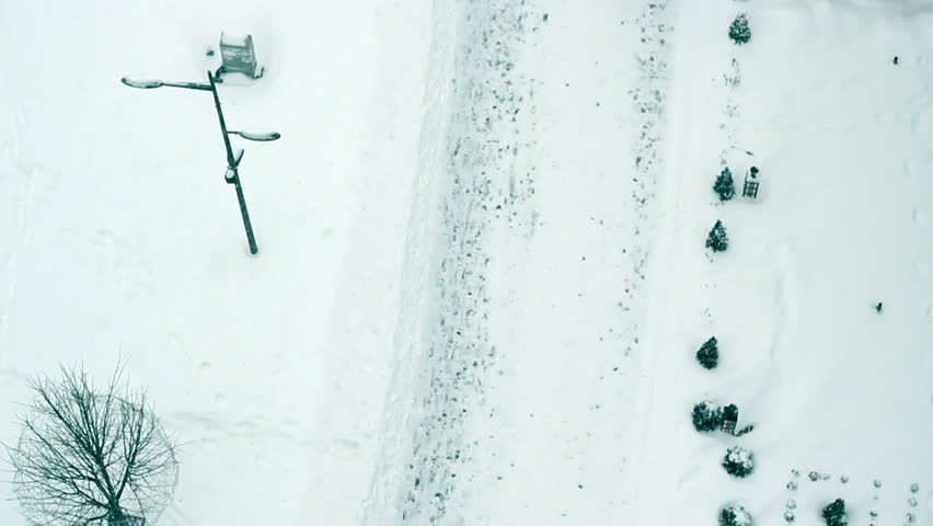 Walking During Snowstorm Bird eye view on a snowy street with people. HD1080p.