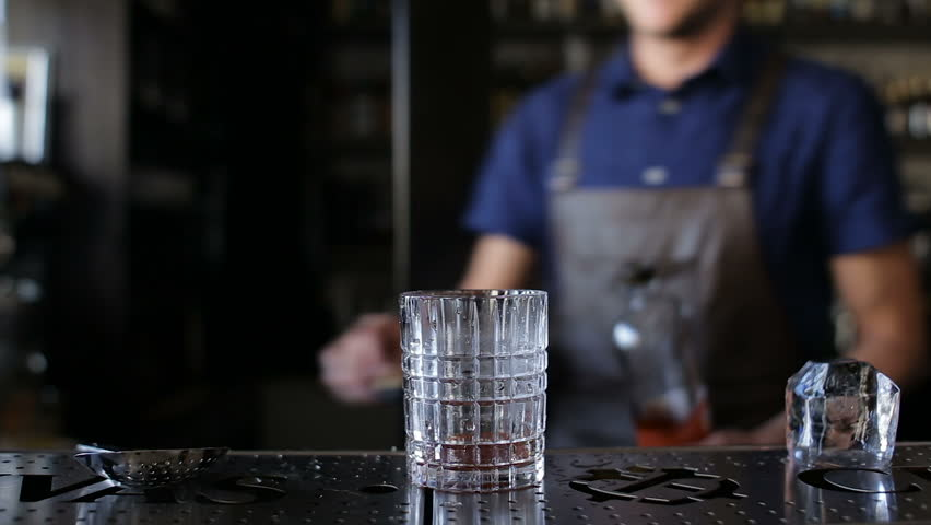 The bartender puts a whiskey in a cocktail | Shutterstock HD Video #19607503
