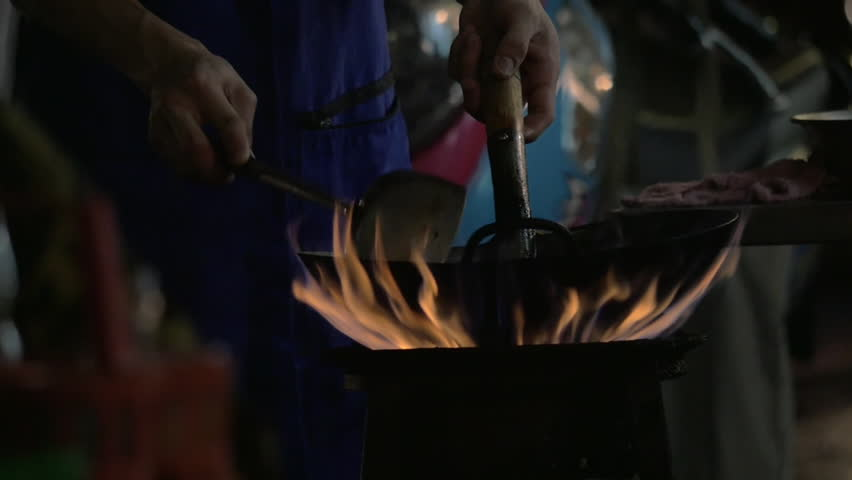 Slow motion shot of a man cooking in the city. Noodle dish in wok made on open fire. Street food in Chinatown of Bangkok, Thailand