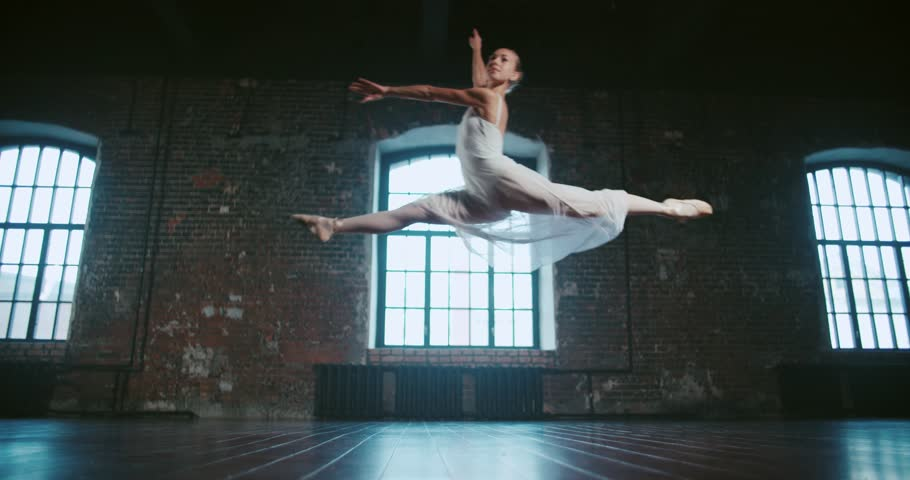 beautiful girl dancer performs a jump, and classical ballet in the loft design Studio,slow motion