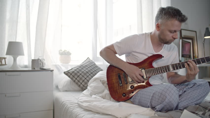 Man playing the guitar and writing down chords on paper while sitting on the bed