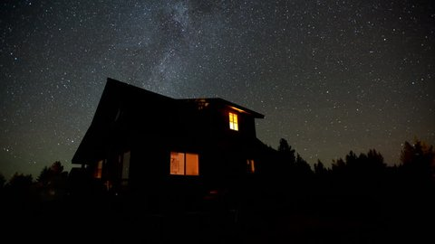 4K time lapse of Milky Way galaxy stars above a rural cabin on a clear calm night in Idaho as the camera frosts over