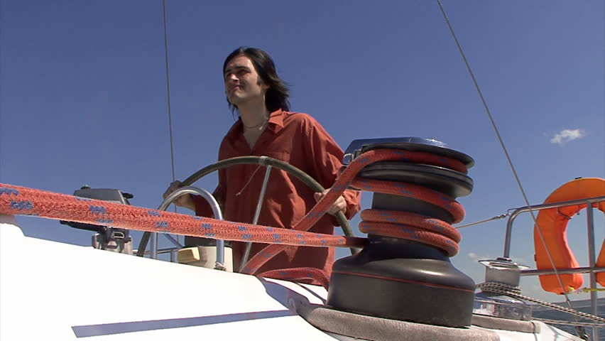 Man steering wheel of the sailboat