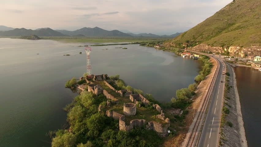 Aerial view at the Lesendro fortifications near transportation dam through the sunset Skadar lake. Route to Podgorica from Adriatic coast. Montenegro