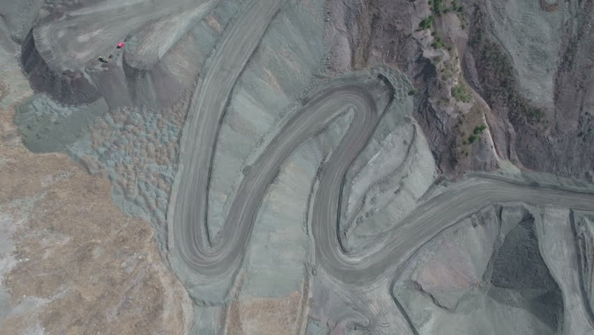 Aerial drone shot flying over grey hairpin roads in an open coal mine pit in China