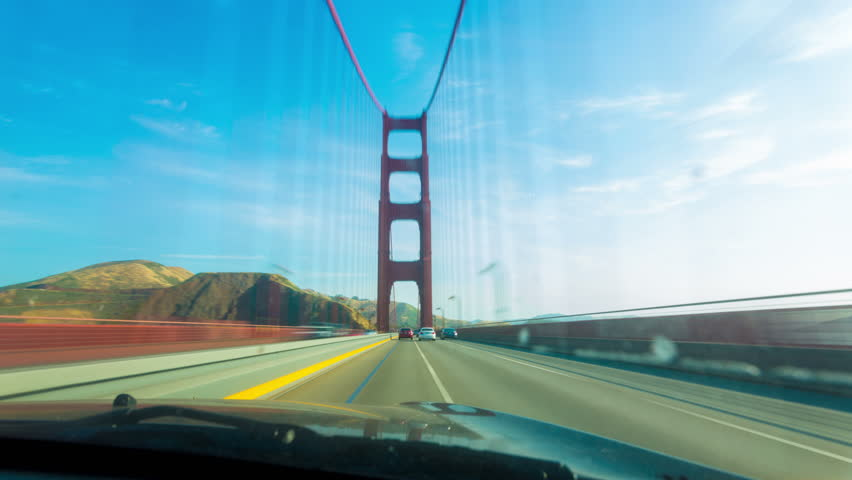 First person point of view, POV, inside car, behind windshield, hood perspective crossing Golden Gate Bridge from San Francisco into Marin driving thru traffic on a blue sky day. 4k 30fps time-lapse