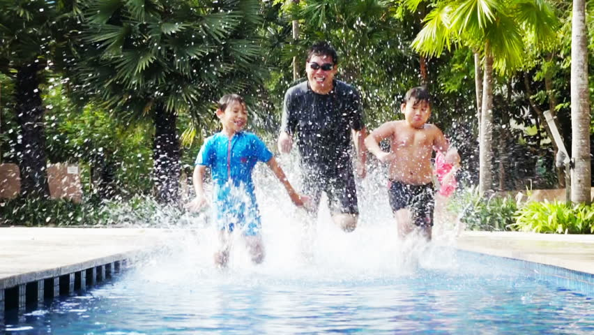 Two Asian boys racing with their father in a pool.