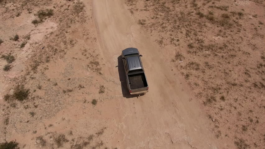 Employees of meteorological services in the SUV moving in the direction of a large hurricane. Texans traveling over rough terrain on a big American pickup truck in the thoron his ranch. Aerial filming