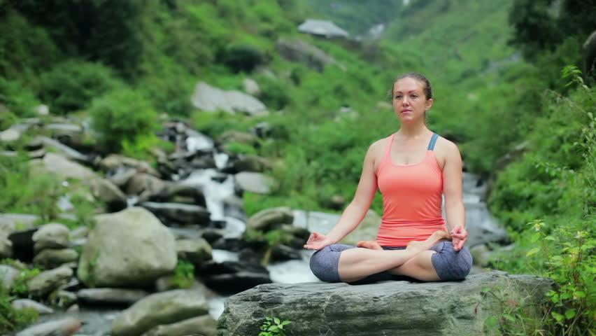 Woman meditating at tropical waterfall in Lotus pose Padmasana | Shutterstock HD Video #19915543