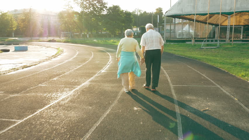 Senior couple taking a walk along the running track in summer. Healthy retirees enjoying morning walking on the stadium with camera lens flare.   Shutterstock HD Video #19927483