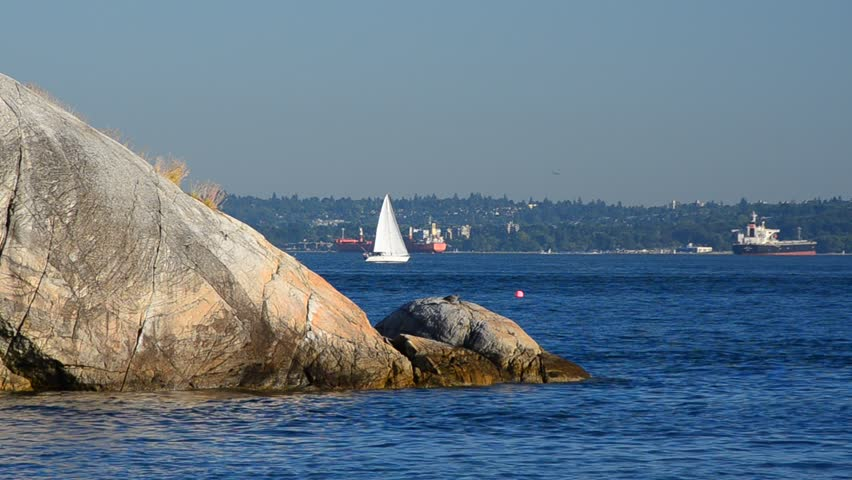 Sailboat and jet crossing in Lighthouse Park at West Vancouver, Canada.