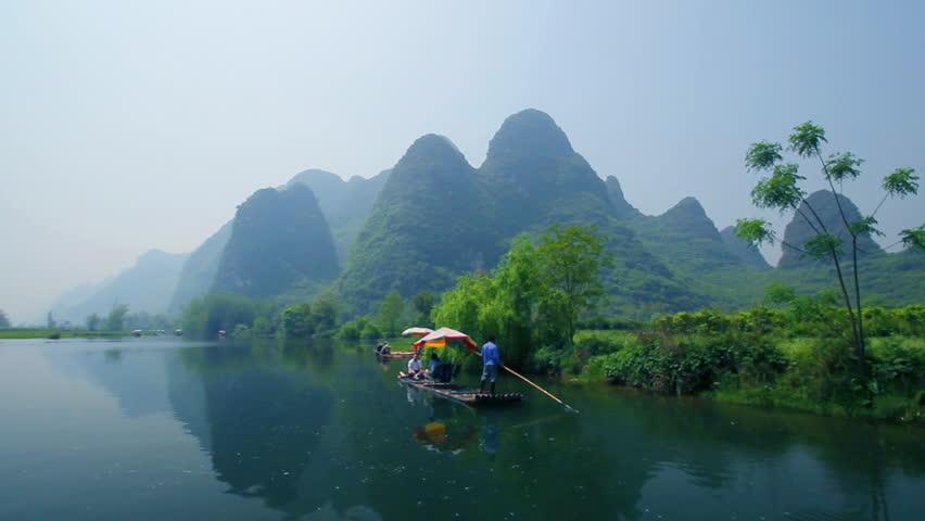 Bamboo raft flowing through the idyllic rural landscape of Yangshuo