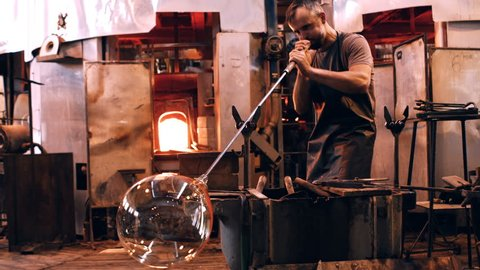 Glassblower free blowing glass at glassblowing factory 4k