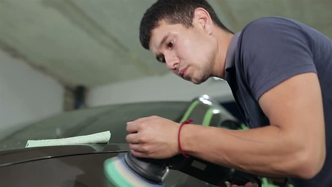 A man polishes the car body