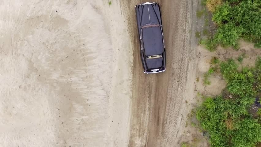 Aerial footage. Pursuit of a vintage car on the sandy shore. The camera follows a car and rises vertically. | Shutterstock HD Video #20050408