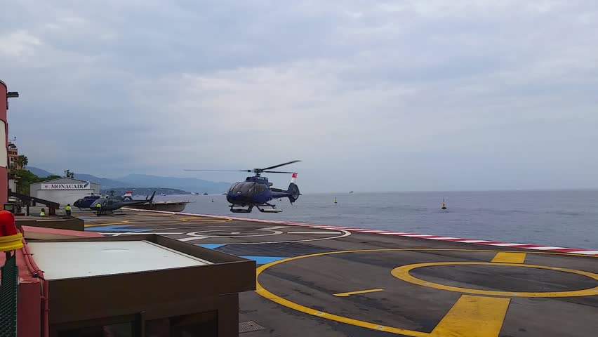 Fontvieille, Monaco - October 01, 2016: Helicopter Landing on the Platform Above the sea in the Monte Carlo International Heliport (Monaco Heliport) in Monaco, French Riviera