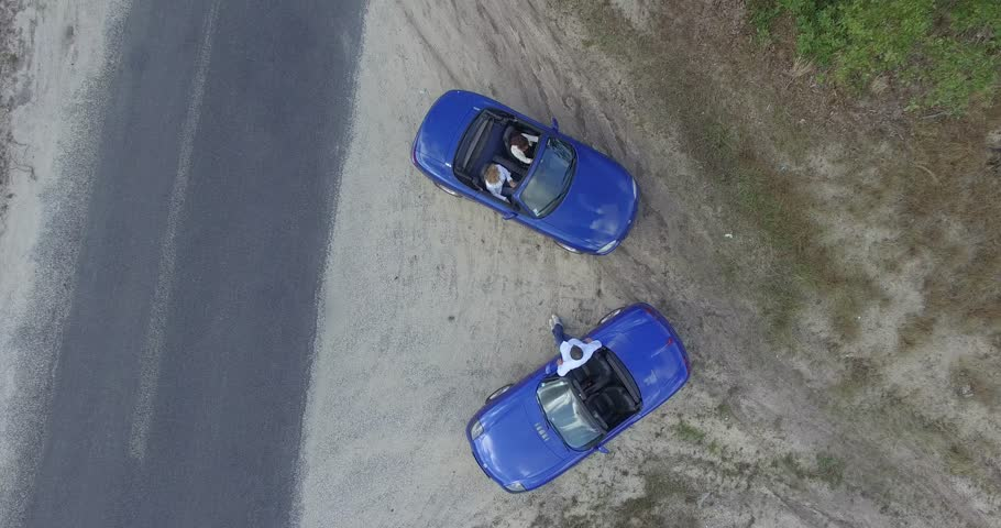 People with two blue convertible car talking on the road | Shutterstock HD Video #20067373