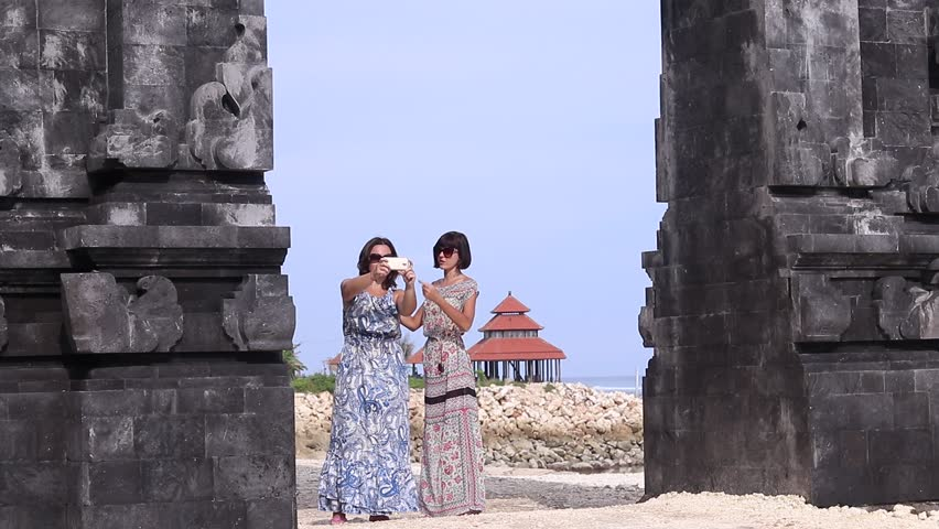 Two young pretty sexy ladies taking a selfie together near the balinese  temple, ocean and summer house on a background. Smiling and laughing.
