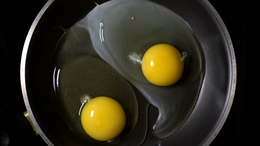Two eggs fried in a pan. Time lapse. Top view.