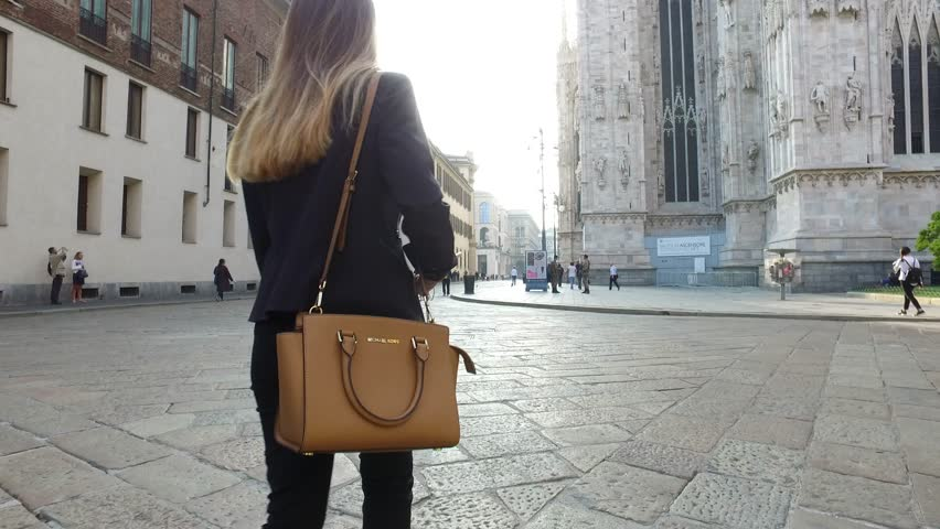 MILAN, ITALY - SEPTEMBER 28, 2016: Young woman walking on the street with a Michael Kors purse. Michael Kors is a luxury handbag and accessories designer for women. Illustrative editorial.