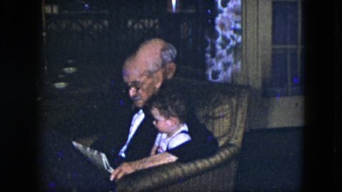 CLEVELAND, OHIO 1951: a grandfather reading the newspaper to his young grandson in a chair