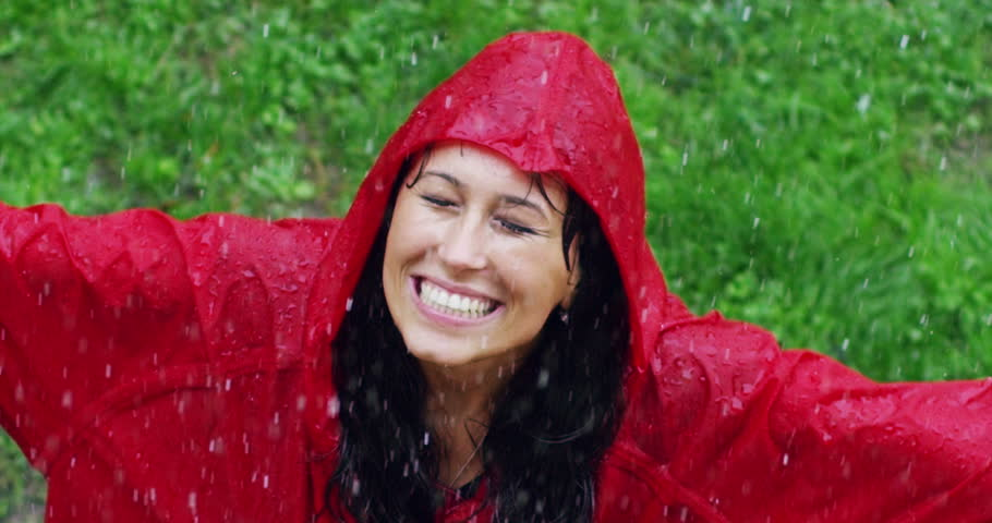 girl smiles, spins and laughs in the rain. the rain falls, the drops fall on his face and the girl is happy with life and nature around. concept of nature and happy life. Adventure, purity. #20125123