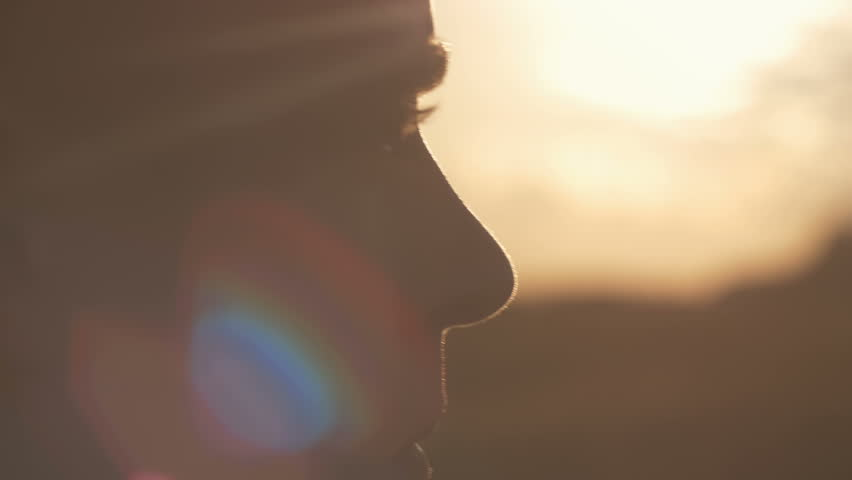 Close-up of man's eyes looking at the sun. Interested man looking for new opportunities as he thinks about the future.