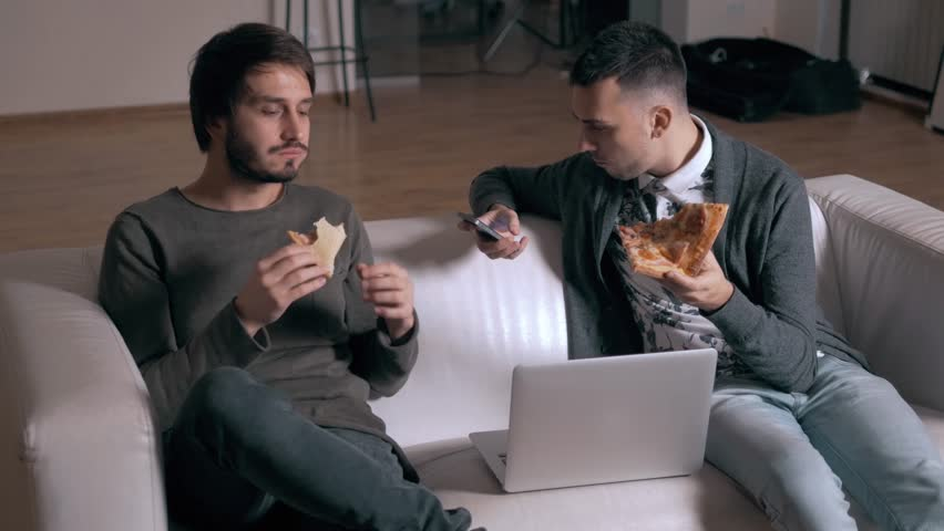 Businessmen in casual style use computers and phones in office and eat pizza from delivery late. Night work and food. | Shutterstock HD Video #20140663