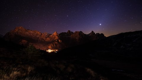 Sweeping dawn time-lapse of valley with a small village nestled at the base of the snowy mountain. The star-filled night sky turns golden as the sun rises through frame. Several shooting stars.
