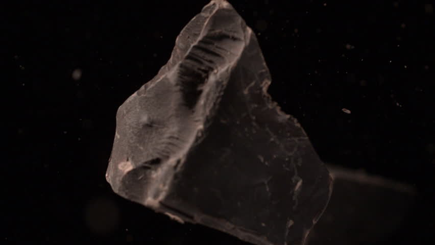 Dark chocolate pieces flying in air out of focus black background in slow motion tabletop