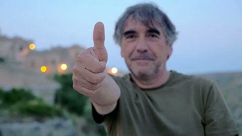 man 50 years old thumbs-up to the camera