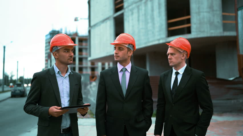 Successful Architects 4k. ultra hd. three young successful architects in orange helmets