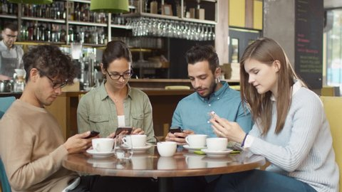Group of Young Mixed race People using Phones in Coffee Shop. Shot on RED Cinema Camera in 4K (UHD).