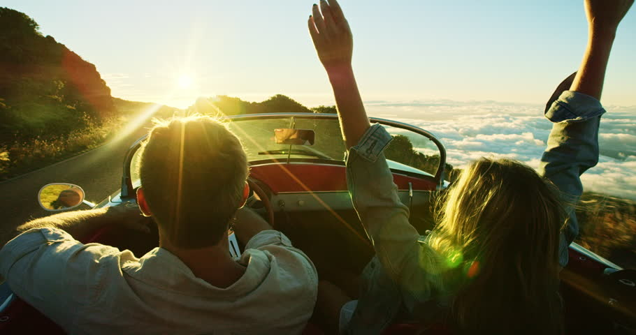 Happy couple driving on country road into the sunset in classic vintage sports car | Shutterstock HD Video #20219053