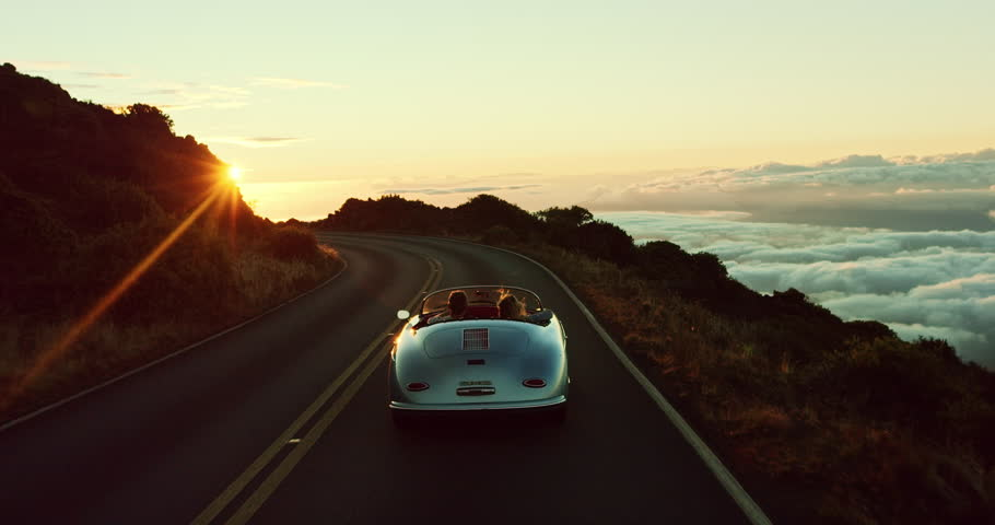 Happy couple driving on country road into the sunset in classic vintage sports car | Shutterstock HD Video #20220283