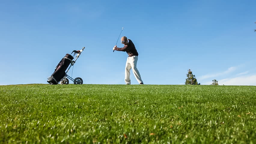 Temperamental golfer throwing a tantrum on the golf course, kicking over his golf cart and throwing his club