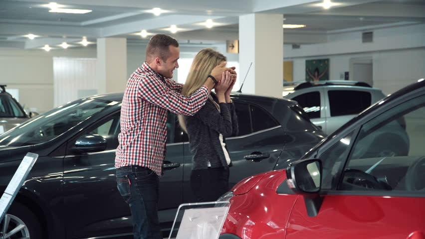 Man Standing Behind Woman and Covering Her Eyes While Standing in front of Shiny New Red Vehicle Inside Car Dealership - Man Surprising Woman with New Car in Show Room.