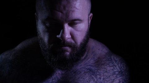 Bald tattoed bearded muscular gangster with a knife. 4K UHD