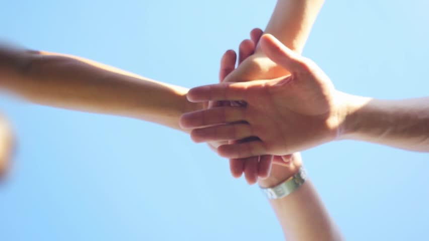 Successful team: many hands holding together on sky background in slowmotion. 1920x1080 | Shutterstock HD Video #20240953