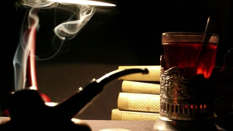Night study interior: a person mixes sugar in a glass of tea in glass-holder, tobacco pipe smoke whirls, a pile of books lie beside under the lamplight