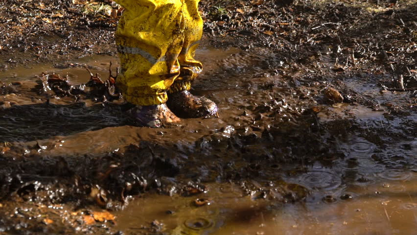 Little girl in a yellow rubber suit is jumping in a puddle.  Slow Motion