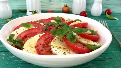 Delicious caprese salad with ripe tomatoes and mozzarella cheese with fresh basil leaves. Italian food. Slow motion.