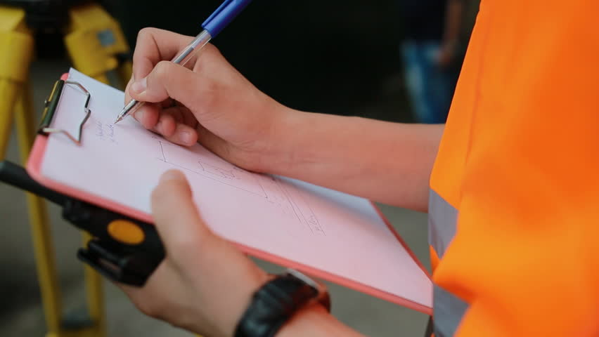 Surveyor makes plan of the land on the paper. Closeup shot.