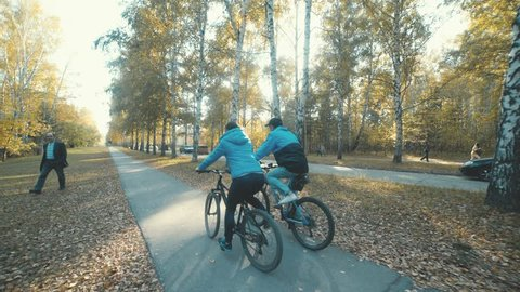 Two bicycle. Couple on bikes. Romantic biking in the autumn forest. Man and woman in similar blue coats. Man and woman riding bikes. Active family leisure. Young couple enjoying cycling through park