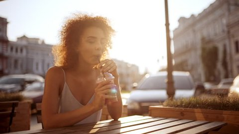 Beautiful redhead girl drinking smoothie smiling resting in cafe Slow motion
