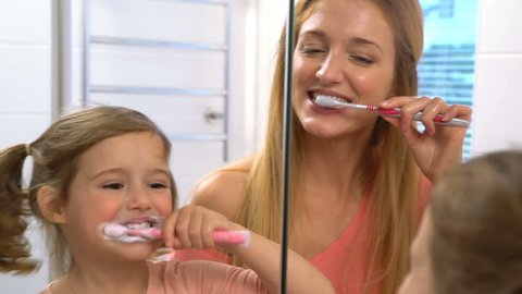 Young attractive mom and her cute daughter brush their teeth in front of the mirror. Slow motion.