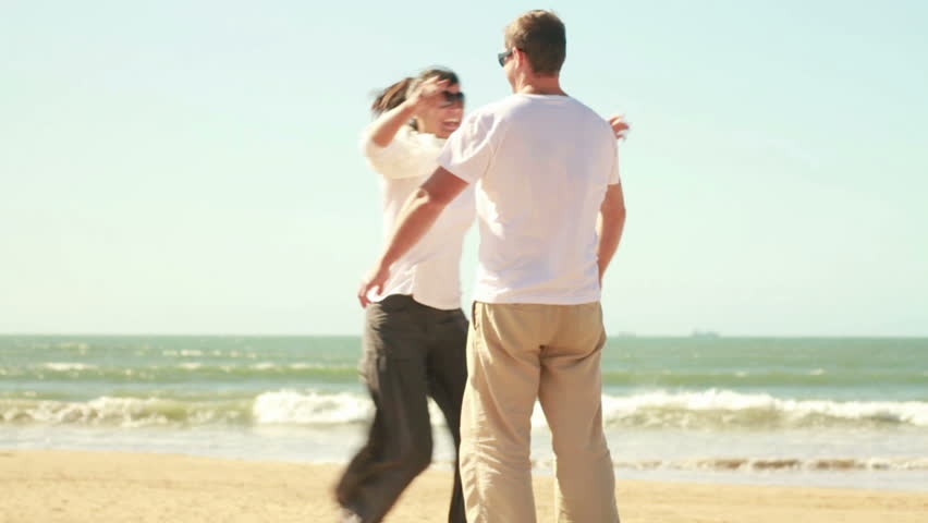 Young happy couple in love at the beach, slow motion